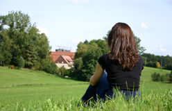 Back home. Young woman sitting in the grass stock photography