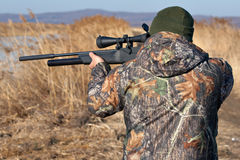 Back hunter. Close up hunter aiming with weapon at the outdoor hunting Royalty Free Stock Photography
