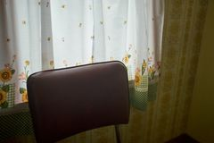Back of a kitchen chair in front of a curtain stock image