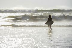 Back light shinny portrait of young happy Asian woman relaxed looking at wild sea waves on sunset tropical beach Royalty Free Stock Photo