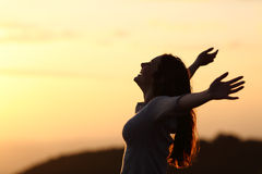 Back light of a woman breathing raising arms. With a warm background stock images