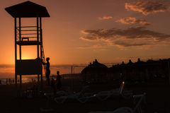 Back lighted lifeguard tower. With sunset over beach Royalty Free Stock Images