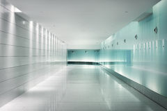 Back-lighted glass walls in an underground futuristic corridor Stock Photo