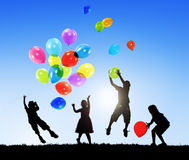 Back Lit Children Playing Balloons Together Outdoors stock images