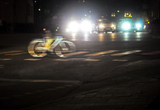 Back lit cyclist. In blurred motion at night Stock Image