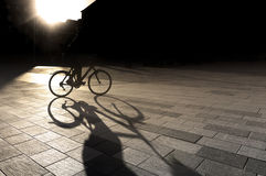 Back lit cyclist. At sunset on square in city, with focus on long shadow Royalty Free Stock Image