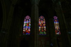 Back-lit pictorial stained glass windows. VIENNA, AUSTRIA - SEPTEMBER 2, 2017; Back-lit pictorial stained glass windows from inside church on dark background Stock Images