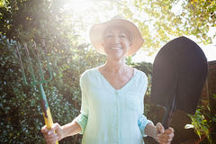 Back lit portrait of smiling senior woman holding garden fork and shovel Stock Image
