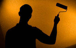 Back lit silhouette of man with paint-roller Royalty Free Stock Image