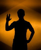 Back lit silhouette of man with raised hand Royalty Free Stock Images