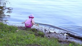 Back of little cute girl in pink sitting on shore of river stock footage
