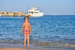 The back of a little girl in a bathing suit on the beach, a yacht at sea stock photos