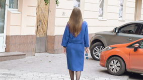 Back look of assured woman walks, turns and smiles on the street. Slowly stock footage