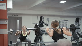 Back look of the girl doing squats with barbell in the gym in 4K stock video