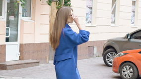 Back look of passionate woman walks, turns and smiles on the street. Slowly stock video footage