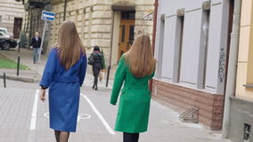 Back look of women walks runway in cashmere coats on the street. Slowly.  stock video