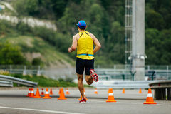 Back male athletic runner running in roads with traffic cones safety. Rosa Khutor, Russia - May 7, 2017: back male athletic runner running in roads with traffic Stock Images