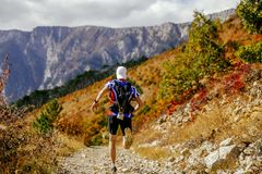 Back male runner running mountain trail. Marathon on background of autumn forest Royalty Free Stock Photos