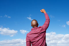 Back of man with arm raised in the air Royalty Free Stock Photo