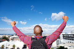 Back of man with bag raising hands in the air Royalty Free Stock Photo