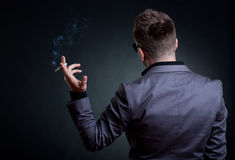 Back of a man with a cigarette in his hand. Over dark background Royalty Free Stock Image