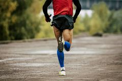 Back man in compression calf sleeves. And sportswear running on road Stock Photos