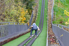 Back of man descending from artificial hill on skis. In helmet at autumn outdoors Stock Photography