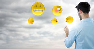 Back of man with emojis and flare against sky with clouds. Digital composite of Back of man with emojis and flare against sky with clouds Stock Photography