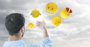 Back of man holding up glass device against cloudy sky with emojis and flare. Digital composite of Back of man holding up glass device against cloudy sky with Stock Image