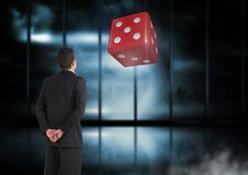 Back of Man Looking at dice. Digital composite of Back of Man Looking at dice stock photo