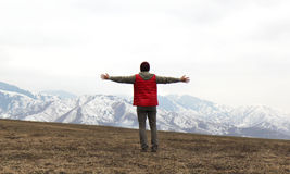 Back of man in red waistcoat with hands to the side on the mountains background royalty free stock photos