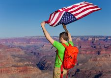 Back of a man with rucksack holding American flag Royalty Free Stock Images