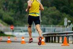 Back man runner running. On road with orange traffic cones Stock Photo