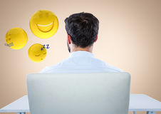 Back of man sitting with emojis against cream background Royalty Free Stock Photos