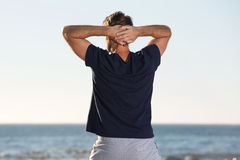 Back of man standing with hands behind head looking at sea Stock Photos