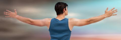 Back of man in training gear with arms out against grey and green Royalty Free Stock Images