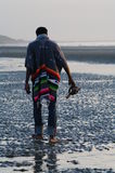 Back of a man walking on Mars. Back of a man walking on a norman beach at low tide Stock Photo