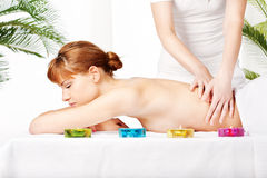 Back massage. Pretty woman getting a back massage in spa salon Royalty Free Stock Images