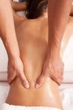 Back massage. Woman enjoy in lower back massage in spa salon Stock Photography