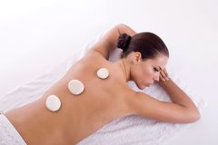 Back massage. Girl getting back massage with stones royalty free stock photos