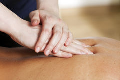 Back massage. Hands of female massage therapist treating a woman's back Stock Photo