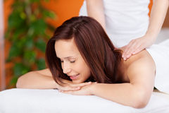 Back massage. Beautiful relaxing woman having a massage in spa Stock Image