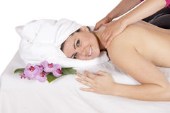 Back massage at day spa by masseuse. Spa therapy getting a back and shoulders massage by technician masseuse for happy pretty young brunette woman, wrapped in Stock Image