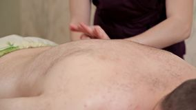 Back massage. Girl masseur in a purple costume makes a relaxing massage