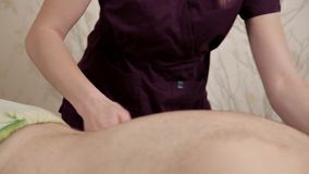 Back massage. Masseur massages the lower back of the male athlete. Girl masseur in a purple costume makes therapeutic
