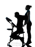 Back massage therapy with chair. One men and women perfoming chair back massage in silhouette studio on white background stock photos