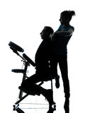 Back massage therapy with chair silhouette. One men and women performing chair back massage in silhouette studio on white background stock photo