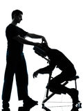 Back massage therapy with chair. Two men performing chair back massage in silhouette studio on white background royalty free stock image
