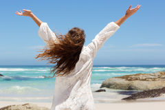 Back of model with arms raised at seaside Stock Photography