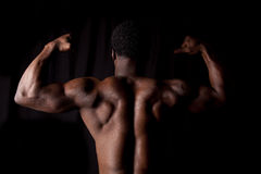 Back muscles. A man showing off his back muscles on a black background Royalty Free Stock Image